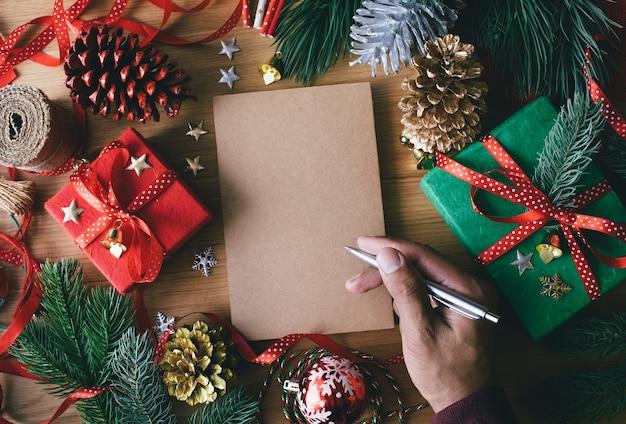 Frohe weihnachtskonzepte mit menschlicher hand, die grußkarten mit geschenkbox vorhanden schreibt