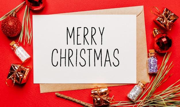 Frohe weihnachtsnotiz mit geschenk, tannenzweig und spielzeug auf rotem isoliertem hintergrund. neujahrskonzept