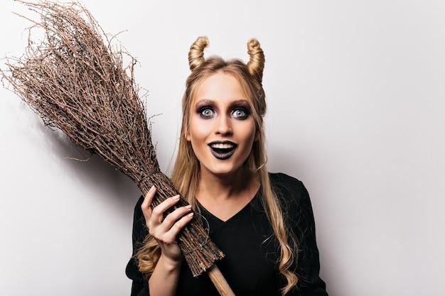 Frohe zauberin, die halloween genießt. überraschte lächelnde hexe mit magischem besen.
