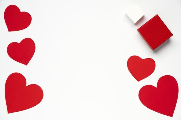 Frohen valentinstag. rote papierherzen mit geschenkboxen auf weiß