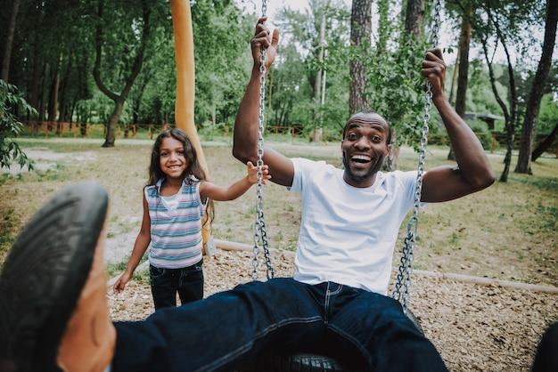 Froher afrikanischer vater auf swing girl swinging dad