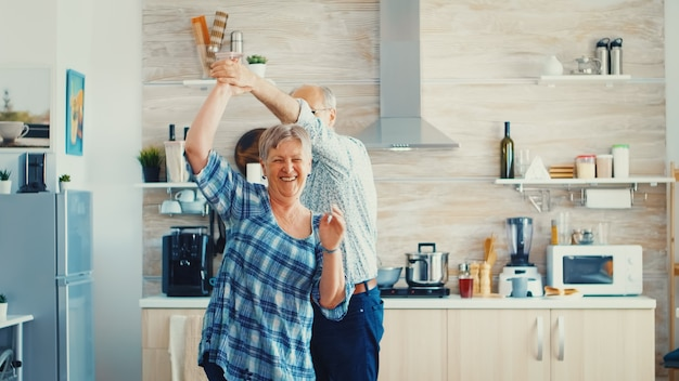 Froher alter alter mann und frau tanzen in der küche. glückliches seniorenpaar, das spaß hat, rentner in einem gemütlichen zuhause, das das leben genießt