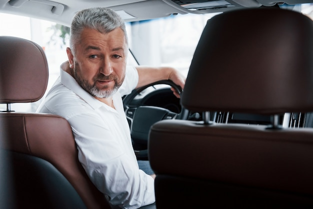 Froher bärtiger mann im weißen hemd beim sitzen im modernen auto