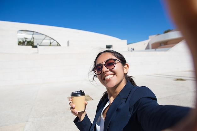 Froher büroangestellter, der mitnehmerkaffee trinkt