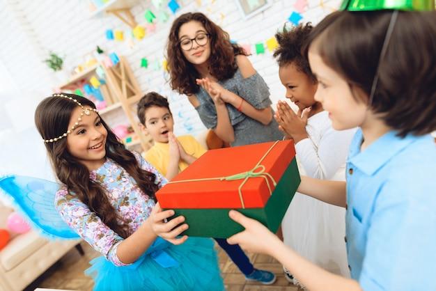 Froher geburtstagsjunge im festlichen hut empfängt geschenk.