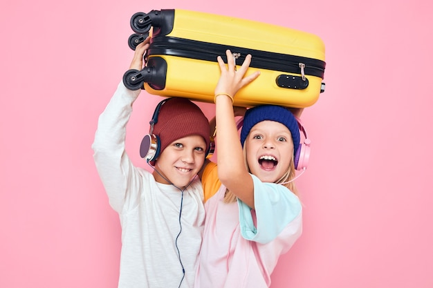 Froher gelber koffer des jungen und des mädchens mit rosafarbenem farbhintergrund der kopfhörer