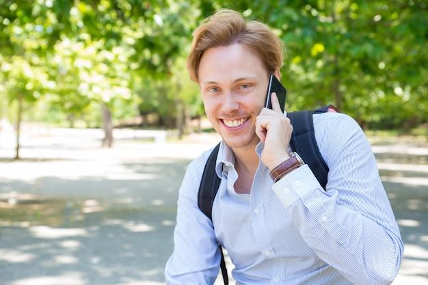 Froher glücklicher studentenkerl, der um telefon im park ersucht