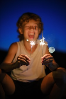 Froher junge mit leuchtenden bengalischen lichtern