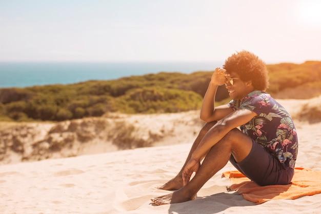 Froher junger afroamerikanermann, der durch seeküste sitzt