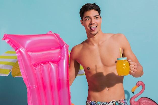 Froher junger mann, der mit getränk und schwimmenmatratze im studio aufwirft