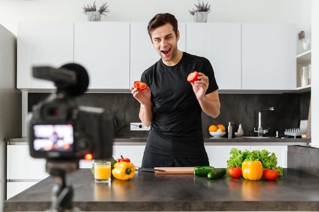 Froher junger mann, der seine videoblogepisode filmt
