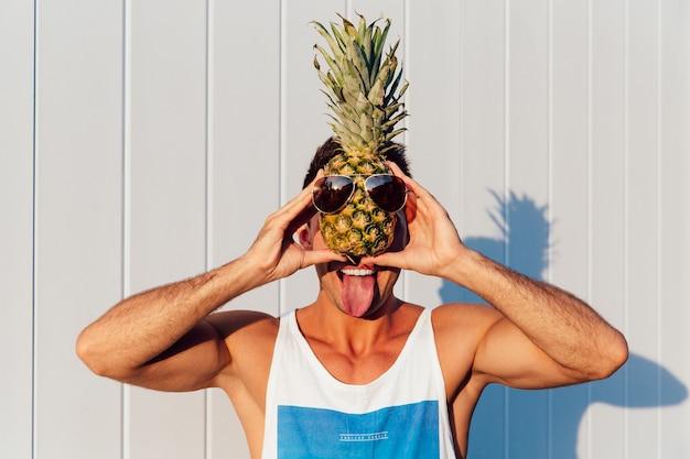 Froher lächelnder mann, der eine zunge, eine ananas mit sonnenbrille halten zeigt