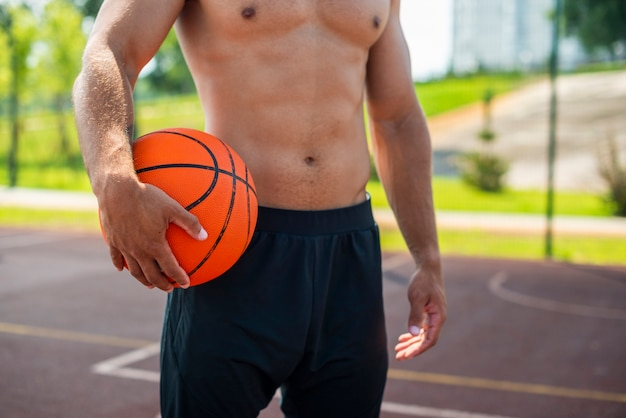 Froher mann, der eine basketballkugel anhält