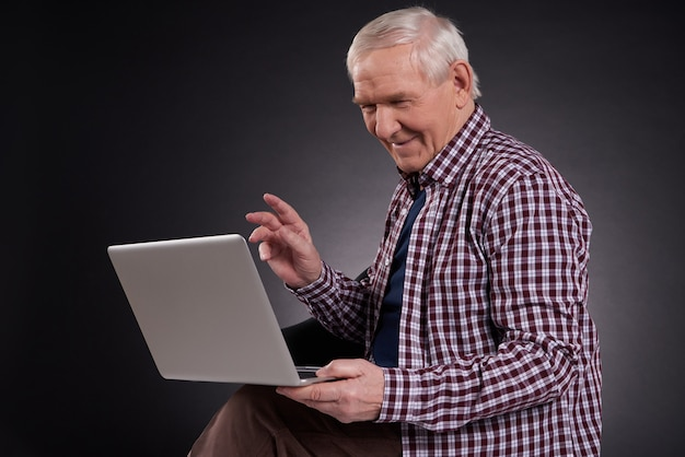 Froher mann, der mit laptop sitzt