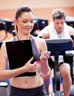 Froher trainer, der ein chronometer mit mann im hintergrund tut körperliche bewegungen hält