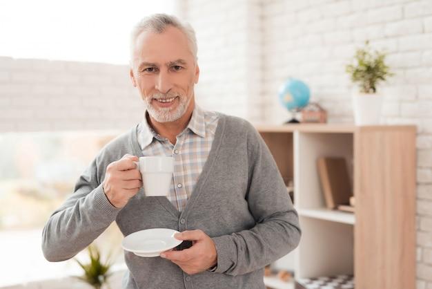 Froher trinkender kaffee des älteren mannes zu hause.