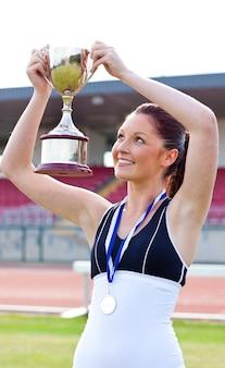 Froher weiblicher athlet, der ein trophee und eine medaille hält