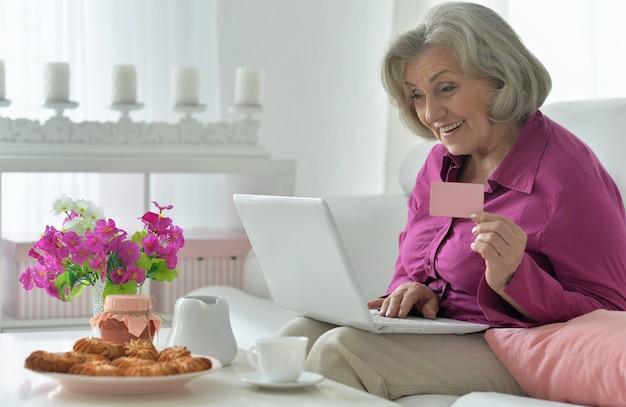 Frohes älteres frauenporträt mit laptop und kreditkarte