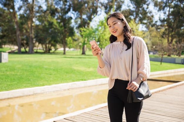 Frohes asiatisches mädchen, das lustige videos am telefon aufpasst
