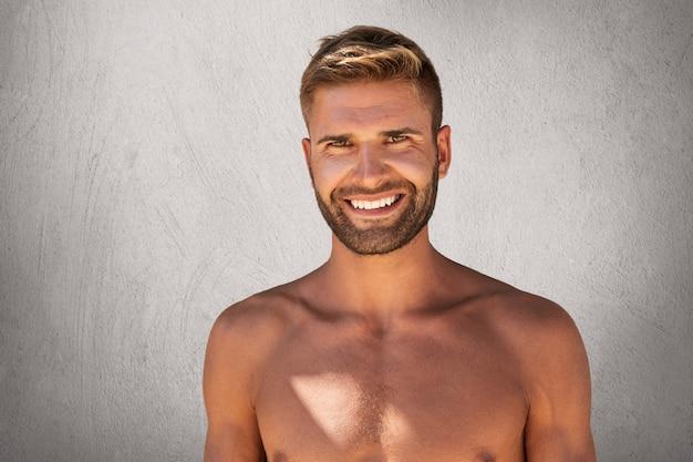 Frohes bodybuilder mit bizeps, der oben ohne mit angenehmem lächeln posiert und glücklich ist, freizeit im fitnessstudio zu verbringen
