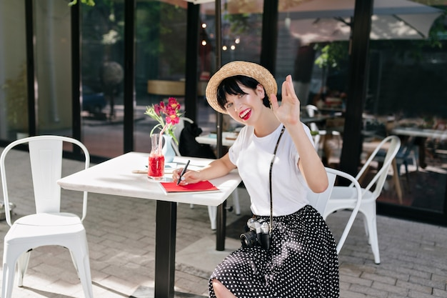 Frohes brünettes mädchen schreibt in notizbuch und winkt hand mit lächeln, im café ruhend