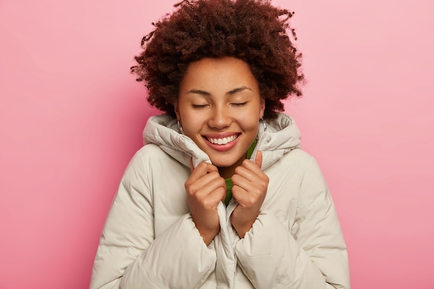 Frohes charmantes mädchen fühlt sich warm in weißer jacke, lächelt breit, hält die augen geschlossen, zeigt perfekte zähne, steht über rosa studiohintergrund