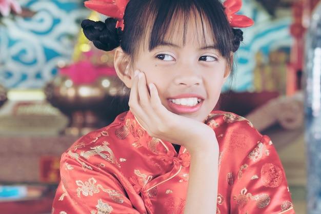 Frohes chinesisches neujahr 2018, nettes asiatisches mädchen im chinesischen kleid, das gott respekt zollt. das neujahrs- oder frühlingsfest ist der wichtigste der traditionellen chinesischen feiertage.