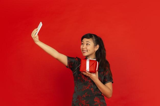 Frohes chinesisches neujahr. asiatisches junges mädchenporträt lokalisiert auf rotem hintergrund