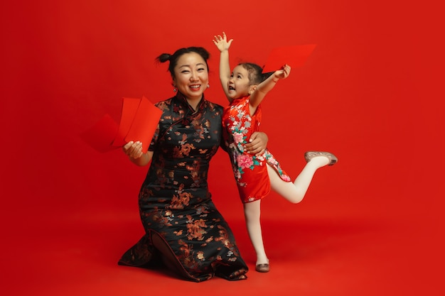 Frohes chinesisches neujahr. asiatisches mutter- und tochterporträt lokalisiert auf rot