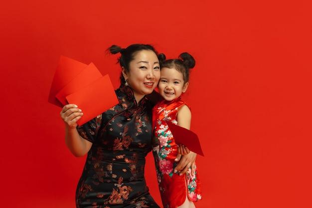 Frohes chinesisches neujahr. asiatisches mutter- und tochterporträt lokalisiert auf rotem hintergrund