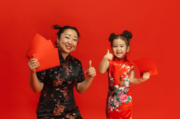 Frohes chinesisches neujahr. asiatisches mutter- und tochterporträt lokalisiert auf roter wand