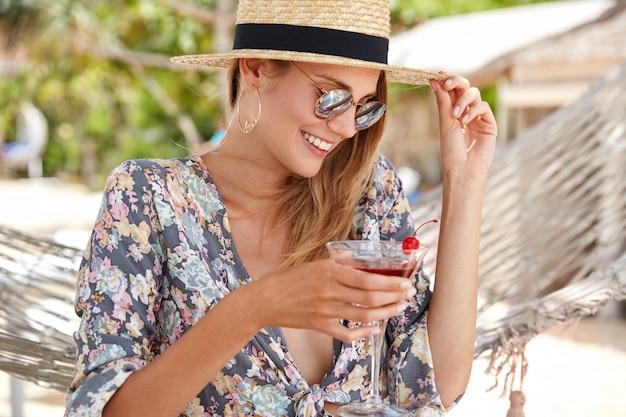 Frohes entspanntes weibliches model fühlt sich aufgeregt, als sie sich im heißen tropischen land im freien neu erschafft, trägt ein hemd mit blumenmuster und einen strohhut, eine trendige sonnenbrille, trinkt einen frischen kirschcocktail,