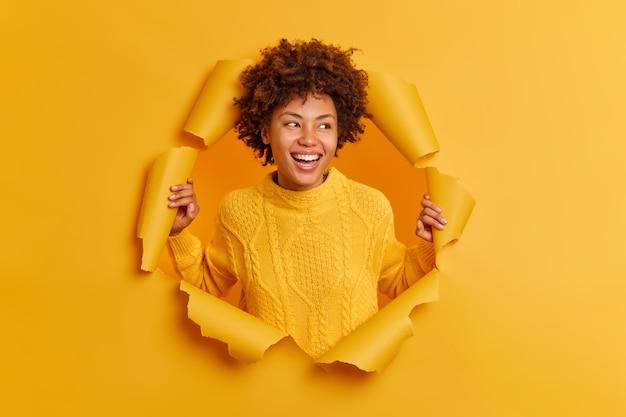 Frohes ethnisches mädchen mit lockigem afro-haar lächelt breit konzentriert beiseite und kichert positiv
