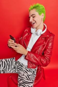 Frohes hipster-mädchen mit gefärbten grünen haaren benutzt handy sendet nachrichten an freunde arrangiert treffen für ein unbeschwertes leben genießt die jugend nutzt coole app auf dem handy sitzt auf dem stuhl hört populäre musik