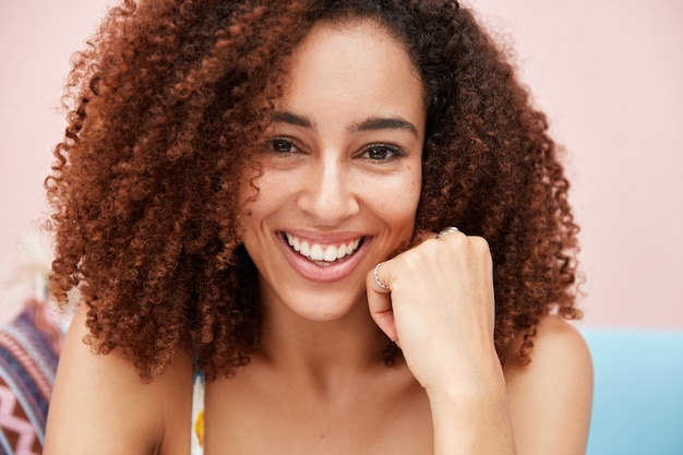 Frohes hübsches junges afroamerikanisches weibliches modell mit breitem sanftem lächeln, hat krauses lockiges buschiges haar, dunkle haut, posiert vor der kamera mit fröhlichem ausdruck