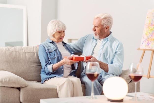 Frohes jubiläum. charmanter älterer mann gratuliert seiner geliebten frau zum hochzeitstag und gibt ihr eine wunderschön verpackte schachtel mit einem geschenk