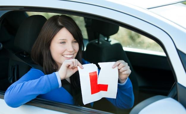 Frohes jugendlich mädchen, das in ihrem auto reißt ein l-zeichen sitzt