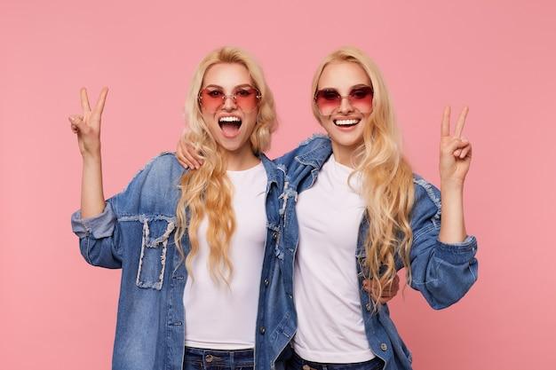 Frohes junges attraktives langhaariges blondes frauen in der sonnenbrille, das hände mit siegesgesten hebt und gern kamera mit charmantem lächeln betrachtet, isoliert über rosa hintergrund