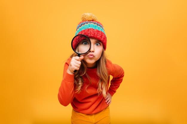 Frohes junges mädchen in der strickjacke und in hut, welche die kamera mit vergrößerungsglas über orange betrachten