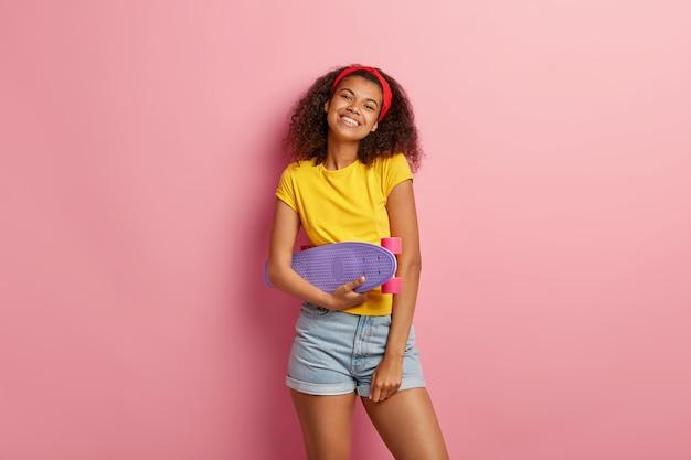 Frohes junges mädchen mit dem lockigen haar, das im gelben t-shirt aufwirft