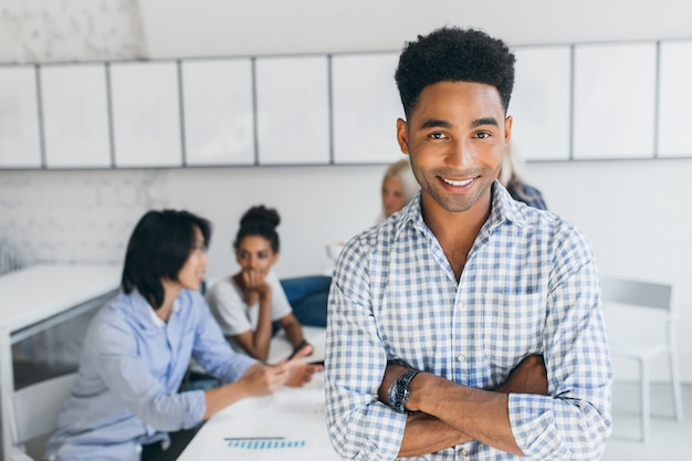 Frohes junges mann mit afrikanischer frisur, die mit verschränkten armen in seinem büro mit anderen angestellten aufwirft. männlicher manager im blauen hemd, das während der konferenz am arbeitsplatz lächelt.