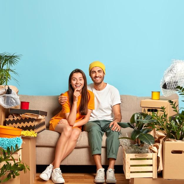 Frohes junges paar, das auf der couch sitzt, umgeben von kisten
