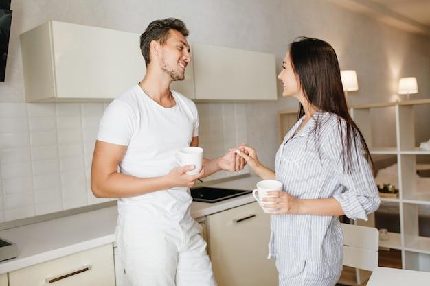 Frohes kaukasisches kerl, das frau hand hält, kaffee in der küche mit weißem innenraum trinkend