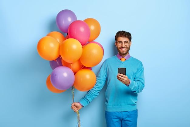 Frohes kerl mit luftballons, die im blauen pullover aufwerfen