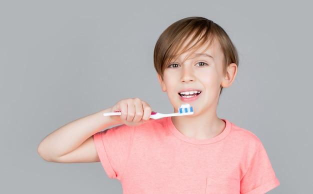 Frohes kind zeigt zahnbürsten. zähneputzen des kleinen jungen. zahnhygiene. glückliches kleines kind, das sich die zähne putzt. kinderjunge, der die zähne putzt. junge zahnbürste weiße zahnpasta. gesundheitsversorgung, zahnhygiene.