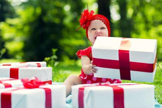 Frohes kindermädchen mit bunten geschenkboxen