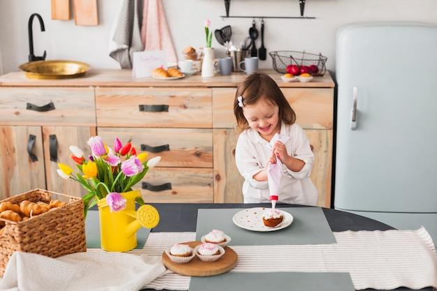 Frohes kleines mädchen, das kleinen kuchen macht