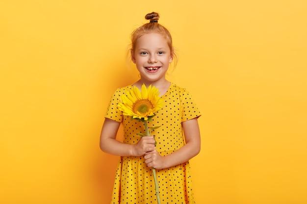 Frohes kleines rothaariges mädchen, das mit sonnenblume im gelben kleid aufwirft