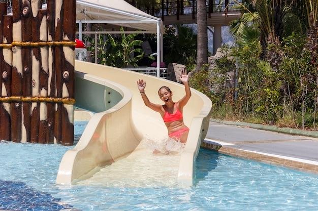 Frohes lachendes jugendlich mädchen geht durch wasserrutsche im hotelaquapark hinunter