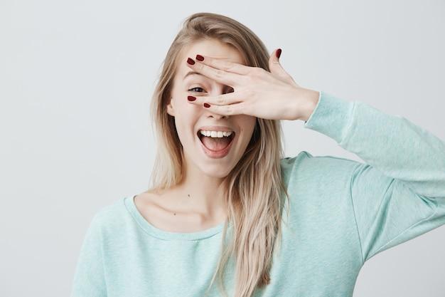 Frohes lächelndes blondes weibliches modell, das ihr gesicht hinter der hand versteckt, hat breites lächeln